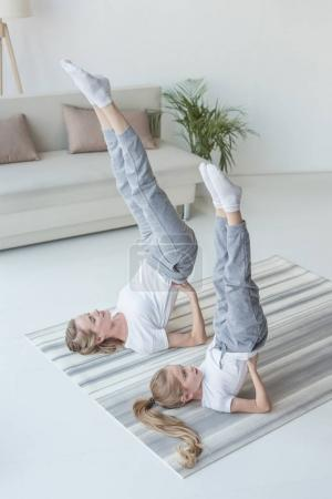 mother and daughter practicing yoga in Supported Shoulder Stand pose at home
