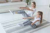 mother and daughter doing v-sit crunches on yoga mat