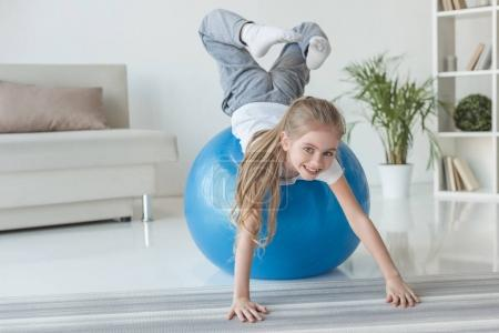 adorable little child playing with fit ball at home