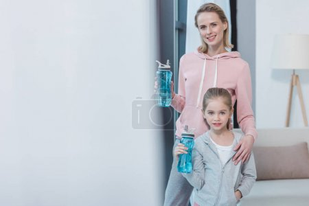 mother and daughter with fitness bottles with water