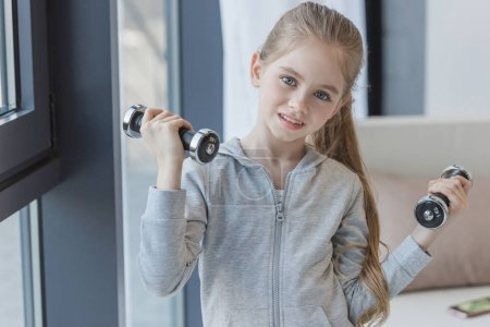 adorable little child working out with dumbbells