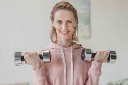 beautiful adult woman working out with dumbbells at home