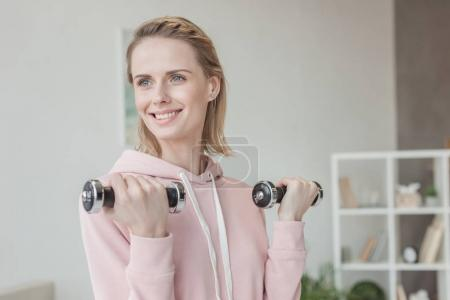 attractive smiling woman working out with dumbbells at home