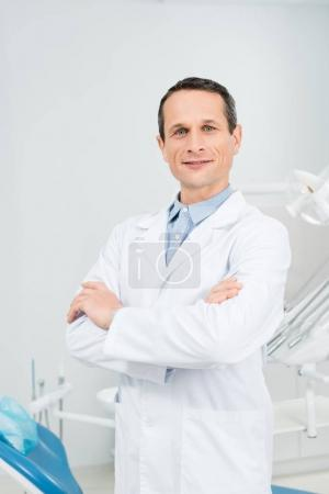 Confident doctor with folded arms in modern dental clinic