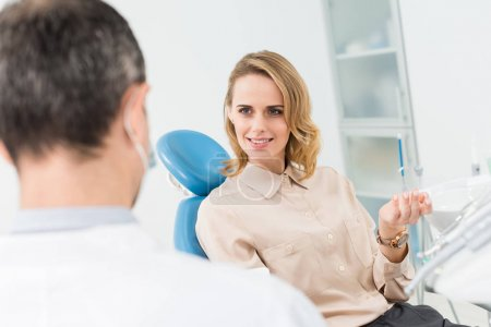 Woman consulting with doctor in modern dental clinic