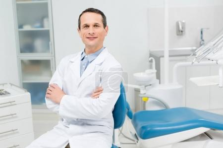 Smiling doctor sitting with folded arms in modern dental clinic