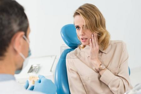 Female patient suffering from toothache in modern dental clinic