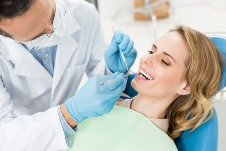 Doctor treats patient teeth in modern dental clini...