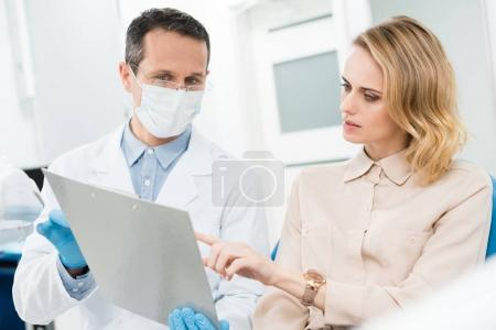 Doctor and smiling patient looking at diagnosis records in modern dental clinic
