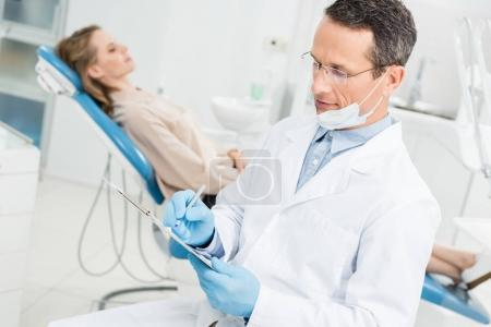 Photo pour Dentiste enregistrant le diagnostic tandis que la patiente attend dans une clinique moderne - image libre de droit