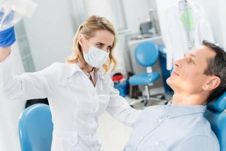 Doctor checking patient teeth in modern dental clinic