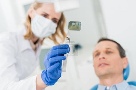 Photo pour Homme consultant avec un dentiste regardant les rayons X dans une clinique moderne - image libre de droit