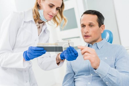 Female doctor and patient choosing tooth implants in modern dental clinic