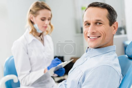 Dentist recording diagnosis while male patient waiting in modern clinic