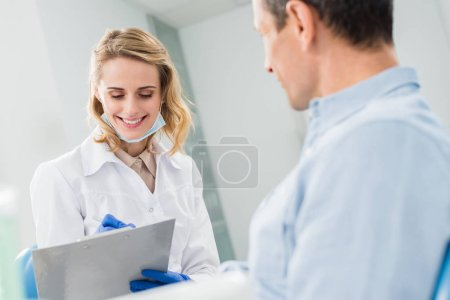 Patient and smiling doctor recording diagnosis in modern dental clinic