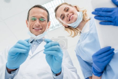 Dentists checking patient teeth in modern clinic