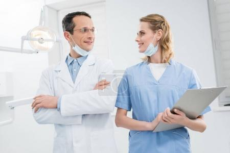 Smiling confident doctors looking at each other in modern dental clinic