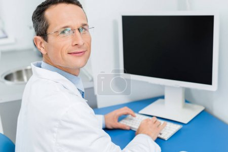 Smiling doctor in glasses working by computer in modern clinic
