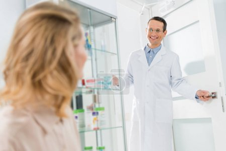 Smiling doctor welcoming female patient in modern dental clinic