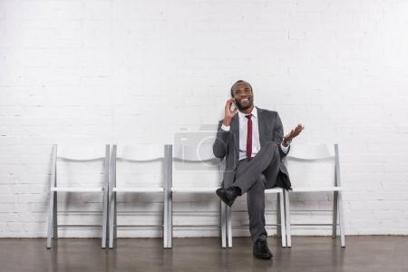 african american businessman talking on smartphone while waiting for job interview