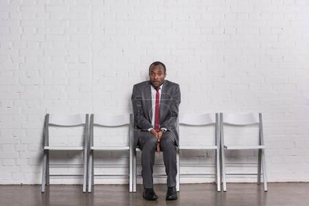 scared african american businessman in suit waiting for job interview