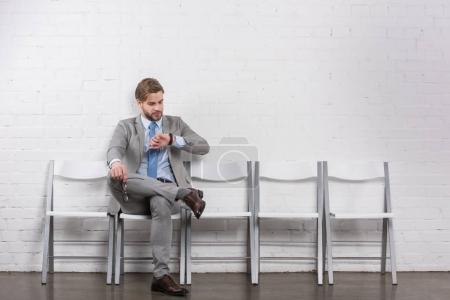 caucasian businessman checking time while waiting for job interview
