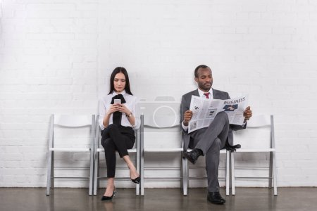 asian businesswoman with smartphone and african american businessman with newspaper waiting for job interview
