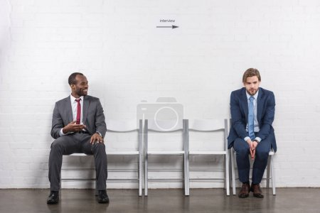 smiling african american businessman looking at scared colleague while waiting for job interview