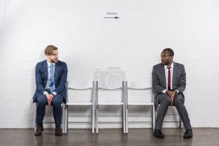 scared multiethnic businessmen looking at each other while waiting for job interview