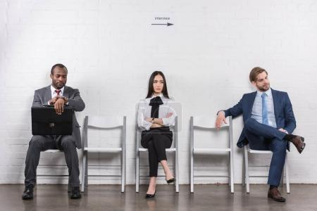 Photo for Multiethnic young business people sitting on chairs while waiting for job interview - Royalty Free Image
