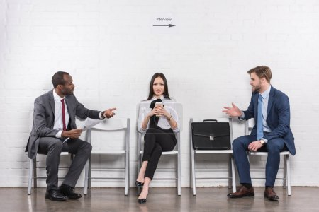 asian businesswoman listening to multicultural businessmen having conversation while waiting for job interview