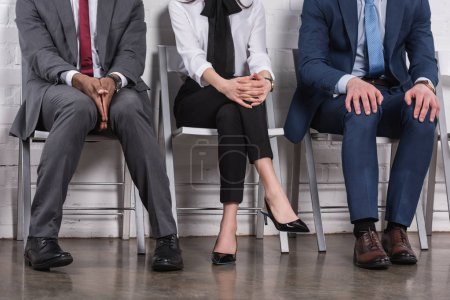 partial view of multiethnic business people sitting on chairs while waiting for job interview
