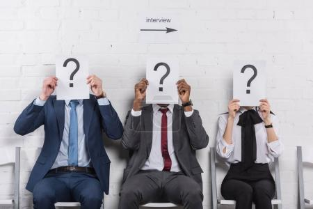 obscured view of multicultural business people holding cards with question marks while waiting for job interview