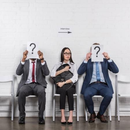 Photo for Asian businesswoman sitting near multicultural businessmen that holding cards with question marks while waiting for job interview - Royalty Free Image