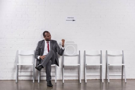 african american businessman showing fist to someone while waiting for job interview
