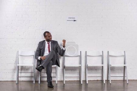 Photo pour Homme d'affaires afro-américain montrant poing à quelqu'un en attendant un entretien d'embauche - image libre de droit