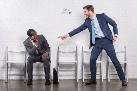 excited caucasian businessman pointing at african american colleague that waiting for job interview