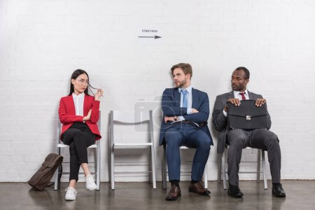 multiethnic business people looking at each other while waiting for job interview