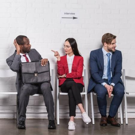 Photo for Multiethnic business people sitting on chairs while waiting for job interview - Royalty Free Image