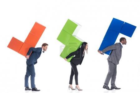 Photo pour Vue de côté de collègues de travail multiculturel tenant des blocs colorés isolés sur blanc, coopération entre entreprises et le concept de travail d'équipe - image libre de droit