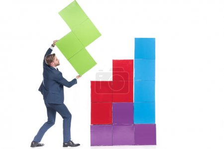 businessman collecting colorful blocks isolated on white