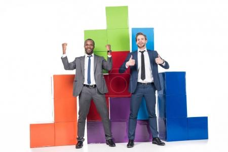 happy multiethnic businessmen standing near colorful blocks isolated on white, teamwork and success concept