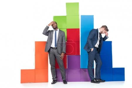 disappointed multiethnic businessmen standing near colorful blocks isolated on white, business cooperation concept