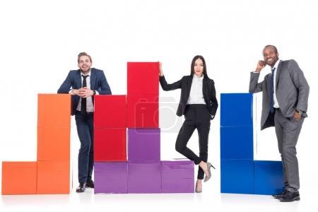 Photo pour Gens d'affaires multiethnique souriant debout près des blocs colorés isolés sur blanc, le concept de travail d'équipe - image libre de droit