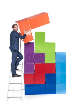businessman on ladder collecting colorful blocks isolated on white