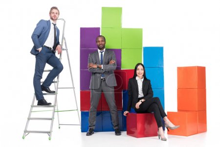 Photo for Multiethnic business people near colorful blocks isolated on white, teamwork concept - Royalty Free Image