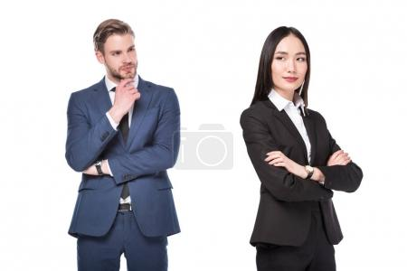 Photo for Pensive businessman looking at asian businesswoman isolated on white - Royalty Free Image