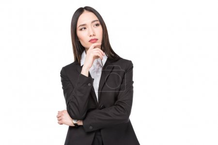 portrait of pensive asian businesswoman in suit isolated on white