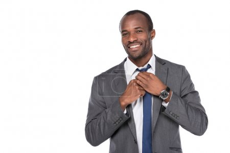 portrait of cheerful african american businessman tying bow tie isolated on white