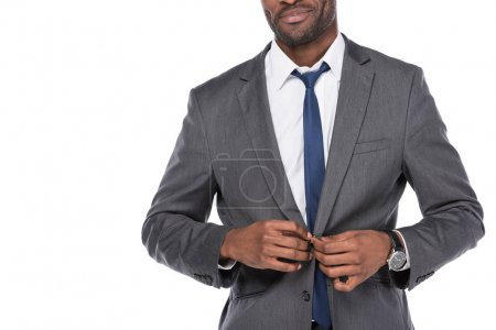 cropped shot of african american businessman buttoning suit isolated on white